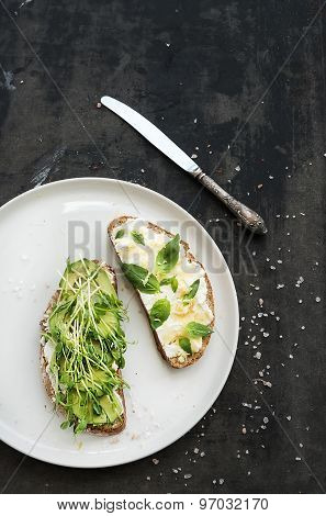 Avocado, ricotta, basil and sprout sandwiches on white ceramic plate over dark grunge backdrop, top