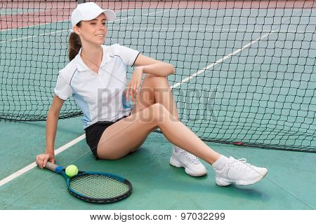 Tennis player sitting on the court surface