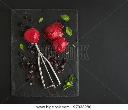 Scoops of berry sorbet or ice-cream with frozen black-currant, mint and metal scooper on black slate