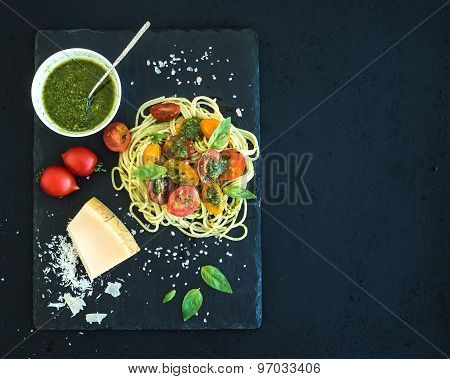 Spaghetti with pesto sauce, roasted cherry-tomatoes, fresh basil and parmesan cheese on black stone