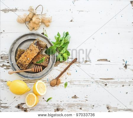 Herbal tea cooking set. Fresh mint, honeycombs, lemon, ginger on rustic white wooden background. Top