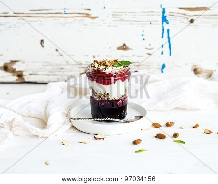 Yogurt oat granola with berries, honey and nuts in glass jar, rustic white  background