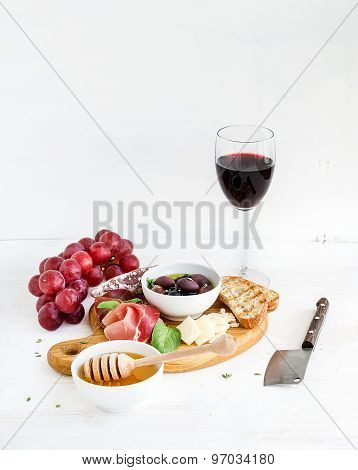 Wine appetizer set. Glass of red, grapes, parmesan cheese, meat variety, bread slices, pecan nuts