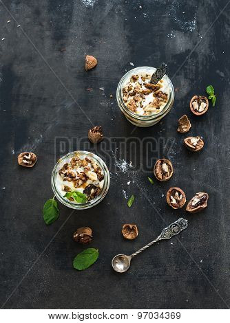 Walnut and salted caramel ice-cream in glass jars with fresh mint over dark grunge backdrop, top vie