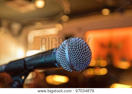 Closeup of audio microphone on stage background