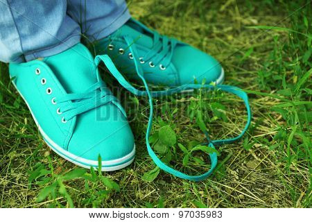 Female feet in gum shoes on green grass background