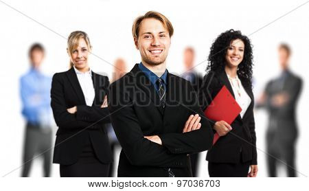 Portrait of a smiling handsome businessman in front of his team