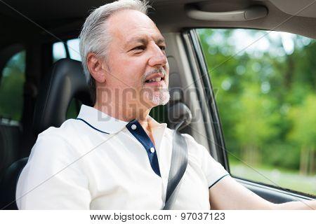 Smiling man driving his car