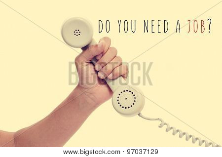 man holding the handset of a telephone and the text do you need a job? with a retro effect