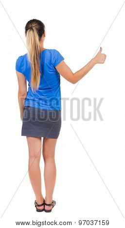 Back view of  woman thumbs up. Rear view people collection. backside view of person. Isolated over white background. Girl in a gray skirt and blue T-shirt shows the right hand thumb up.