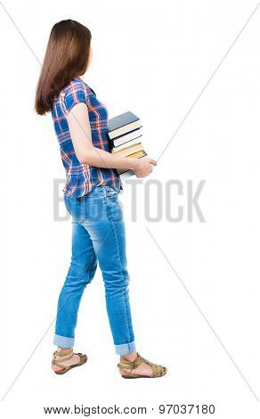 girl carries a heavy pile of books. side view. Rear view people collection. backside view person. young girl in checkered blue with red stripes stands sideways and holding a stack college textbooks.