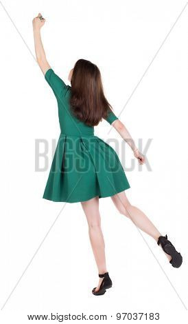 back view of writing beautiful woman. Young girl in dress. Rear view people collection.  backside view of person. The girl in stylish green dress standing on tiptoes writes a felt-tip pen on top.