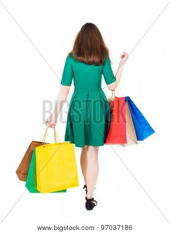back view of going  woman  with shopping bags . beautiful girl in motion.  backside view of person.  Isolated over white background. girl in stylish green dress is holding shopping bags on bent elbow