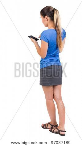 back view of standing young beautiful  woman  in vest and using a mobile phone. girl  watching.  Isolated over white background. Girl in a gray skirt and blue shirt running on the phone.