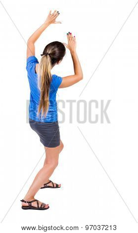 back view of woman  protects hands from what is falling from above. . Girl in a gray skirt and blue shirt covered his hands on top of something falling.