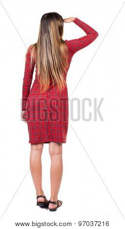 back view of standing young beautiful  woman.  girl  watching. Rear view people collection.  Isolated over white background. Long-haired girl in a red plaid dress covers her eyes with her hand