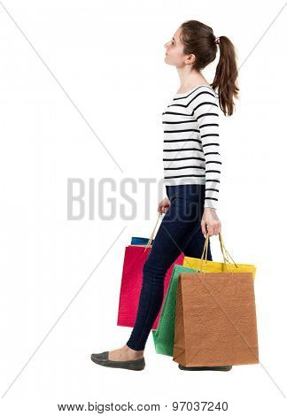 back view going  woman  with shopping bags . beautiful girl in motion. backside view of person. Isolated over white background. Frenchwoman in the vest goes right with shopping bags and looking upward