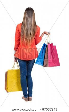 back view going woman in  jeans woman with shopping bags. beautiful girl in motion.  backside view of person. Isolated over white background. Girl in red jacket holding in each hand with shopping bags