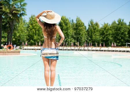 Woman holding an hat in front of a pool