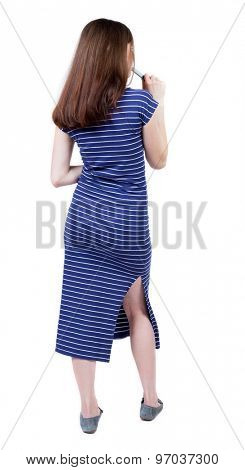 back view of young beautiful girl standing in thoughtful pose. Rear view people collection.  Isolated over white background. Girl in a blue striped dress with a felt-tip pen is thoughtfully.