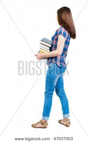 A girl carries heavy pile of books. side view.  Rear view people collection.  backside view person. young girl in checkered blue with red stripes stands sideways and holding a stack college textbooks