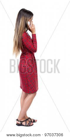 back view of standing young beautiful  woman and using a mobile phone. girl  watching.  backside view of person.  Isolated over white background. Long-haired girl in a red plaid dress talking on phone