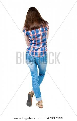 back view of standing young beautiful  woman.  girl  watching. Rear view people collection.   Isolated over white background. A young girl in a checkered blue with red stripes is bent right leg.