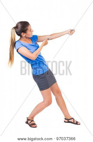 back view of standing girl pulling a rope from the top or cling to something. girl  watching. Isolated over white background. Girl in a gray skirt and blue shirt pulling the rope something heavy right