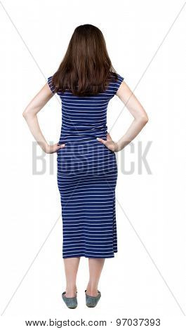 back view of standing young beautiful  woman.  girl  watching. Rear view people collection.  backside view of person Girl in a blue striped dress is putting hands on waist and looking thoughtfully.