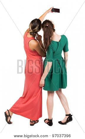 Back view of two young woman photographed on a mobile phone. Rear view people collection. Rear view. Isolated over white background. Two girlfriends are photographing themselves on the phone.