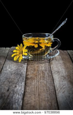 Herbal tea with yellow daisy on wooden table