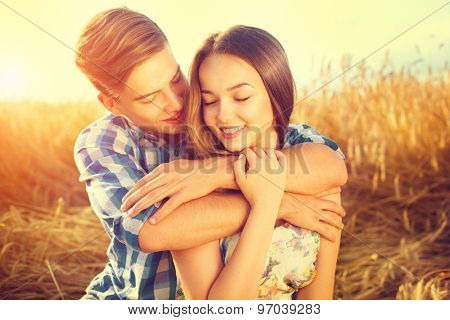 Beauty Couple relaxing on wheat field together. Happy girlfriend and boyfriend having fun outdoors, kissing and hugging, love concept. Beautiful Boy and Girl in love together
