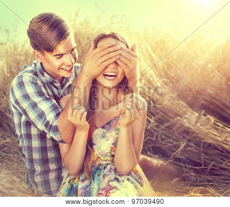Beauty Couple relaxing on wheat field together. Teenage girlfriend and boyfriend having fun outdoors, kissing and hugging, love concept. Teenagers Boy and Girl in love together