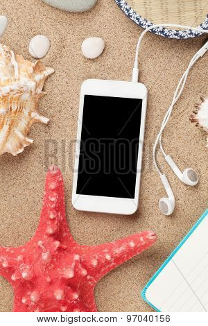 Smartphone on sea sand with starfish and shells. Top view with copy space