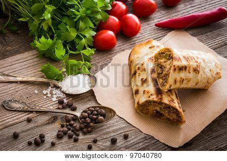 burrito on parchment with vegetables and spices on a wooden background