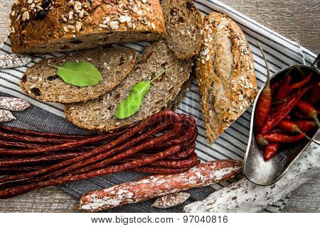 Wholemeal bread with dried sausages on a  table