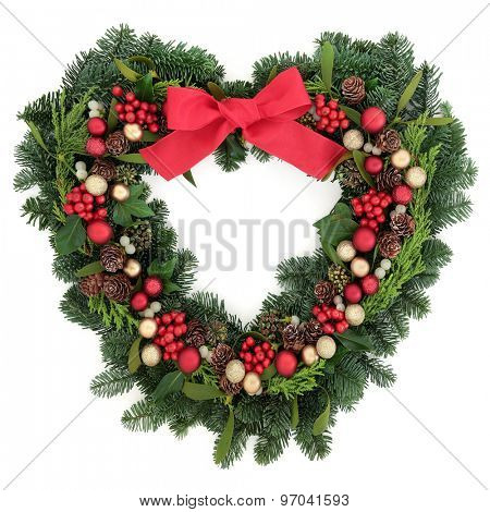 Christmas heart shaped wreath with bauble decorations, holly mistletoe, ivy, pine cones and winter greenery over white background.