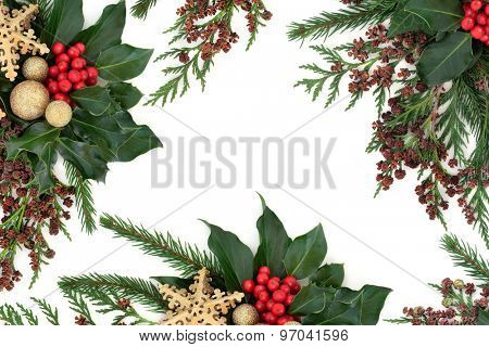 Christmas flora with gold  baubles, holly with red berries, ivy, fir and winter greenery over white background.
