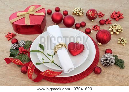 Christmas dinner place setting with plates, napkin, red baubles, holly, mistletoe, fir and gift box over light oak background.