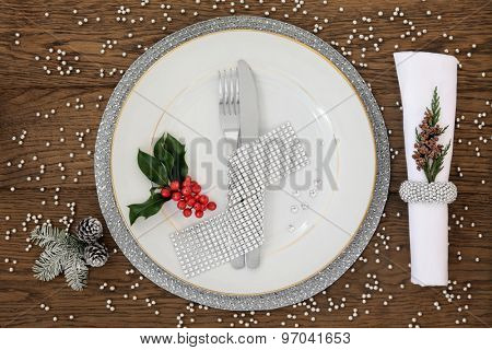 Christmas holiday dinner place setting with plate, napkin, cutlery, silver bauble decorations with holly over oak table background.