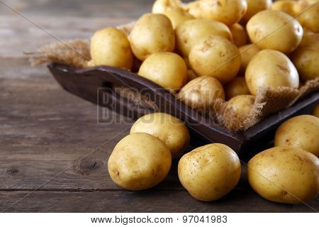 New potatoes in tray on wooden table, closeup