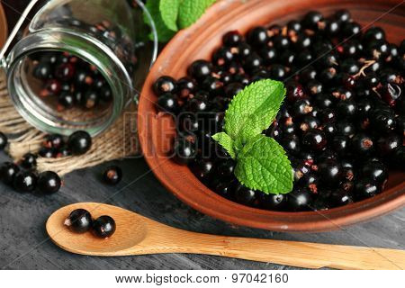 Ripe blackcurrant and tasty jam on wooden background