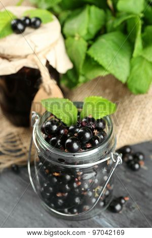Ripe blackcurrant in glass jar and tasty jam on wooden background
