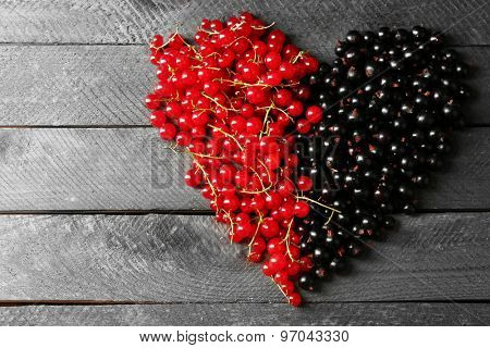 Heart made with forest berries on wooden background