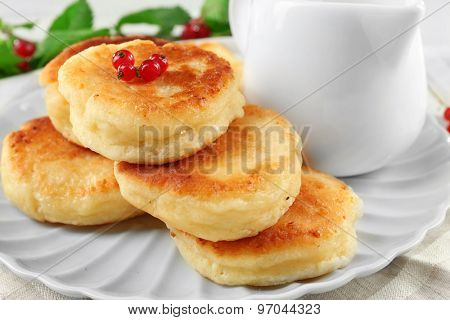 Fritters of cottage cheese with red currant in plate on table, closeup
