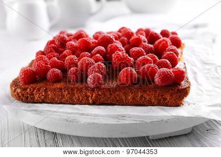Fresh pie with raspberry on wooden tray, closeup