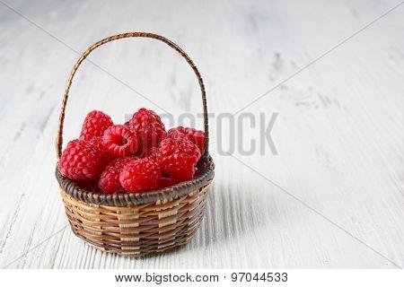 Fresh red raspberries in wicker basket on wooden background