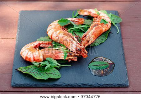 Grilled shrimps on slate plate, outdoor shot