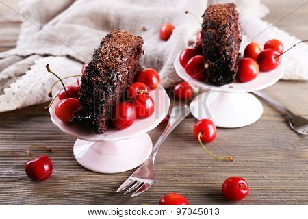 Delicious chocolate roll with cherries in saucer on wooden background