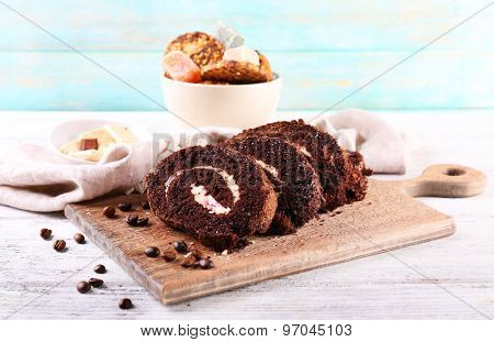 Delicious chocolate roll on cutting board on wooden background